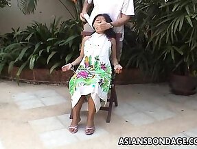 Asian teen tied up and hand cuffed on a chair